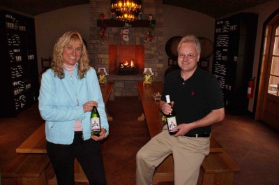 Matt & Sandy Downey Holding Wine Bottles at Magnus Ridge Winery